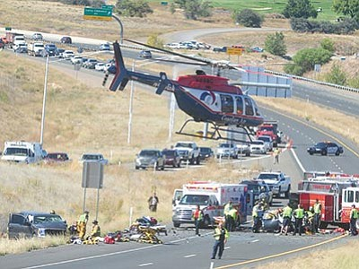 Les Stukenberg/The Daily Courier<br> Helicopters airlifted the three victims of this two-vehicle collision near the Highway 89A and Granite Dells Parkway onramp Monday morning. Prescott Police, Fire, Central Yavpai Fire, Lifeline Ambulance, and Department of Public Safety personnel responded to the head-on collision.