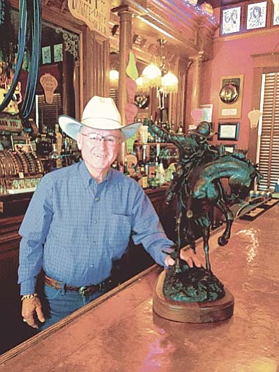 Cindy Barks/The Daily Courier<br>Tommy Meredith, owner of the Jersey Lilly Saloon, displays a bronze sculpture depicting a cowboy and horse in a battle for control by noted western sculptor Bradford Williams. Those who donate $25 or more to the fundraising effort will have a chance to win the bronze, estimated at a value of $4,900.