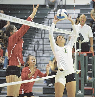 Matt Hinshaw/The Daily Courier<br> Yavapai's Jordan Tilley tips the the ball over the net while Mesa's Megan Block, far left, tries to block her Wednesday night at Yavapai College in Prescott.