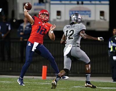 Arizona quarterback Anu Solomon, left, throws a pass while pursued by Colorado defensive back John Walker in the second half of an NCAA college football game Saturday, Oct. 17, 2015, in Boulder, Colo. Arizona won 38-31. (AP Photo/David Zalubowski)