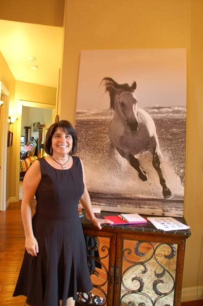 Artist Jody L Miller poses next to one of the 12 pieces of artwork she created for her new collection, Windswept Manes. The collection features horses on the beach and will be shown in the Arts Prescott Gallery, 134 S. Montezuma, Prescott, starting Nov. 4. (Photos by Max Efrein/The Daily Courier)