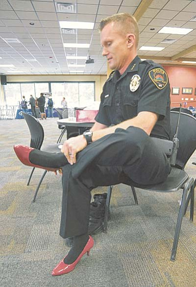 Matt Hinshaw/The Daily Courier<br>Prescott Valley Police Department Deputy Chief James Edelstein puts on a pair of high heel shoes before walking a mile in them Wednesday afternoon at Embry-Riddle Aeronautical University in Prescott.