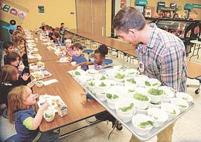 Les Stukenberg/The Daily Courier<br>Yavapai County Health Department's Brad Goss hands out cups of spinach to first graders at Coyote Springs, as part of the Farm to School event.