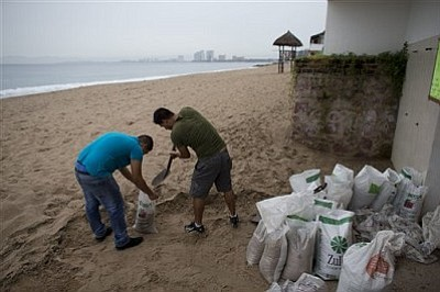 "Men fill small bags with sand from the beach as they prepare for the arrival of Hurricane Patricia in Puerto Vallarta, Mexico, Friday, Oct. 23, 2015. Patricia headed toward southwestern Mexico Friday as a monster Category 5 storm, the strongest ever in the Western Hemisphere that forecasters said could make a ""potentially catastrophic landfall"" later in the day. (AP Photo/Rebecca Blackwell)"