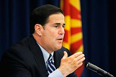 In this photo made on Wednesday, Oct. 21, 2015, Arizona Gov. Doug Ducey addresses the Arizona Commerce Authority prior to meeting with reporters to explain that his plan to use state land trust cash to boost school funding is changing as his office engages in talks with lawmakers and educators. The Arizona Senate has begun debate Friday on a package of bills that will pump $3.5 billion into K-12 education over 10 years and settle a five-year-old lawsuit filed by schools. (AP Photo/Ross D. Franklin)
