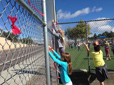 Abia Judd Elementary School students Josie Savoini, left, Ava Nolte and Taft Mangum tie red ribbons on the fence at the school as part of Red Ribbon Week festivities. (Courtesy photo)