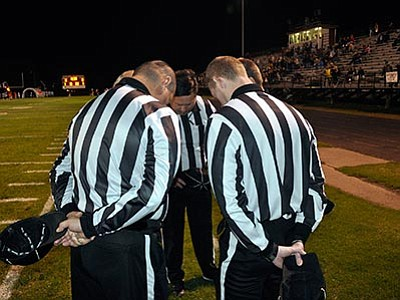 Kurt Voigt/The AP<br> Referee Greg Knight, center, leans in for a pre-game prayer with other officials before a high school football game in Gentry, Arkansas.