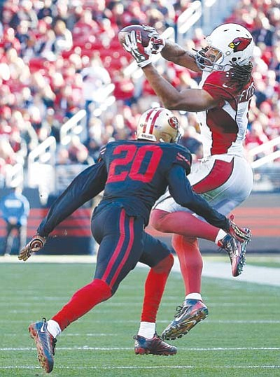 Arizona Cardinals wide receiver Larry Fitzgerald (11) catches a pass in front of San Francisco 49ers cornerback Kenneth Acker (20) during the first half in Santa Clara, Calif., Sunday, Nov. 29. (Tony Avelar/The Associated Press)