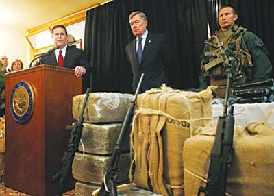 AP Photo/Ross D. Franklin<br>With seized drugs and weapons from border-crossing drug smugglers, Arizona Gov. Doug Ducey, left, speaks at a news conference after testifying at a field hearing of the U.S. Senate Homeland Security and Governmental Affairs Committee at the Arizona Capitol Nov. 23 in Phoenix.  R. Gil Kerlikowske, center, commissioner of the U.S. Customs and Border Protection, listens in during the news conference.