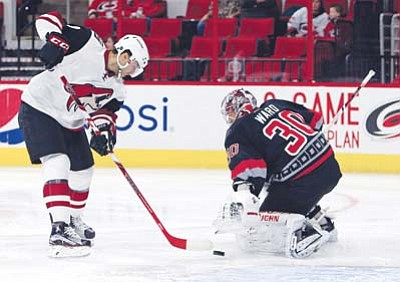 Arizona Coyotes' Tobias Rieder (8) puts the rebound from Carolina Hurricanes goalie Cam Ward (30) into the net for a goal during the first period, Sunday, Dec. 6, in Raleigh, N.C. (AP Photo/Karl B DeBlaker)