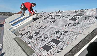 Matt Hinshaw/The Daily Courier<br>Adam Denesovies with M&M Roofing installs shingles on top of the Elks Opera House in downtown Prescott Tuesday afternoon.