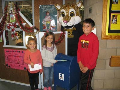 Courtesy photo<br /><br /><!-- 1upcrlf2 -->The Abia Judd replica blue postal box and is flanked by first-grader Adiana Chunglo and second-grader Olivia Raber on the left, ready to mail letters; school mascot Jazzy Jaguar behind; and fourth-grader Samuel Bennett on the right.