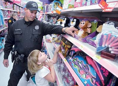 Bailey Wright, 7, looks at a stuffed animal while shopping with Department of Public Safety Trooper Glen Huddleston Saturday morning during the 18th Annual Shop with a Cop event at the Highway 69 Wal-Mart in Prescott. (The Daily Courier)