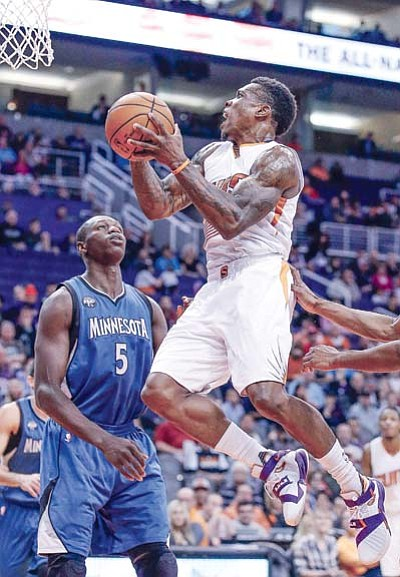 Phoenix Suns' Eric Bledsoe, right, drives past Minnesota Timberwolves' Gorgui Dieng (5), of Senegal, during the first half  Sunday, Dec. 13, in Phoenix. (AP Photo/Ross D. Franklin)