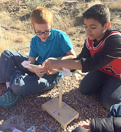 Briana Lonas/Tribune<br> Lake Valley Elementary fifth-graders Hunter Goff  and Anthony Morales study the effects of wind friction during their Schoolyard Habitat program last week.