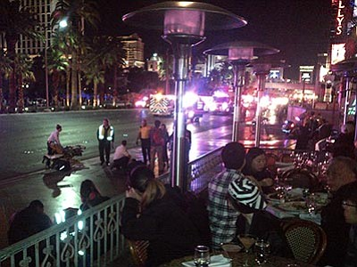 Justin Cochrane via AP<br> People crowd on a sidewalk while police cars and ambulances gather on a street after a car drove onto a busy sidewalk and mowed down people outside a casino in Las Vegas, Nevada, Sunday, Dec. 20. A woman intentionally swerved her car onto a busy sidewalk two or three times and mowed down people outside a Las Vegas casino, police said.