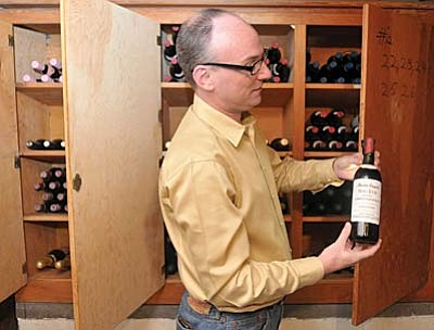 Prescott 12-11-15<br /><br /><!-- 1upcrlf2 -->Matt Hinshaw/The Daily Courier<br /><br /><!-- 1upcrlf2 -->Jeff Hardin CEO/Owner of the Pine Cone Inn holds up one of the many antique bottles of wine he found with Bud Tyndale, Music Director/Owner and Jimbo Weisenhunt of Prescott Lock and Safe in the basement of the Pine Cone Inn Friday afternoon in Prescott.  The bottles of wine date back to 1971 and were in a locked cabinet for several years until Weisenhunt gained access recently.