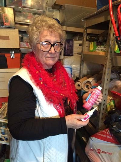 Jean Lutz, founder of Everybody's Place, holds up some just-donated craft supplies she found in her storage unit that is stocked with donated and recycled supplies intended to benefit homeless artists.