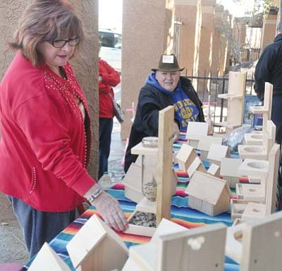 Navy Veteran Richard Findlay talks about his woodwork with Bessamac Cunningham Saturday afternoon, Nov. 28, during the Holiday Sale Arts & Crafts off Iron Springs Road in Prescott.