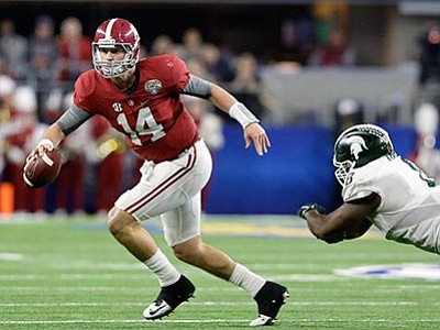 LM Otero/The AP<br> Alabama quarterback Jake Coker escapes the grasp of Michigan State defensive lineman Lawrence Thomas during the Cotton Bowl on Thursday, Dec. 31, in Arlington, Texas.