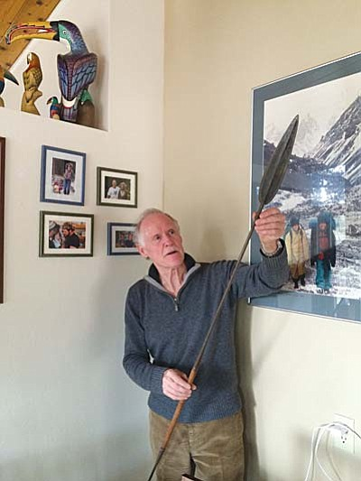 Nanci Hutson/The Daily Courier<br>Roy Smith holds up an African spear in his Prescott home where his walls are filled with photos of adventures he has experienced over some 40 years of worldwide travel.
