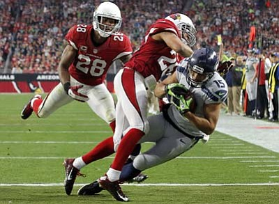 Seattle Seahawks wide receiver Jermaine Kearse (15) falls into the end zone for a touchdown as Arizona Cardinals free safety Rashad Johnson (26) and cornerback Justin Bethel (28) defend during the first half Sunday, Jan. 3, in Glendale. (AP Photo/Ross D. Franklin)
