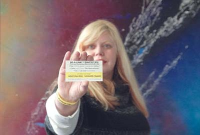 Tina Blake, development coordinator for West Yavapai Guidance Clinic Foundation, displays a Yellow Ribbon card, the key component to a suicide prevention program adopted by the clinic as part of its efforts to reduce suicide rates in Yavapai County. (Les Bowen/The Daily Courier)<br /><br /><!-- 1upcrlf2 -->