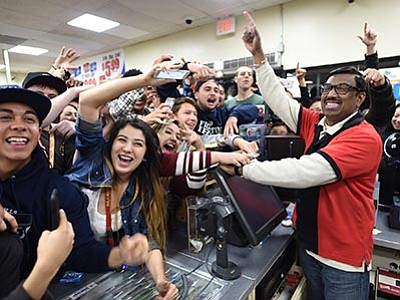Will Lester/The Sun via AP<br> 7-Eleven store clerk M. Faroqui celebrates with customers after learning the store sold a winning Powerball ticket on Wednesday, Jan. 13, in Chino Hills, California. One winning ticket was sold at the store located in suburban Los Angeles said Alex Traverso, a spokesman for California lottery. The identity of the winner is not yet known.