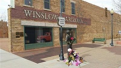 """In this Tuesday, Jan. 19, 2016, photo courtesy of Tom McCauley, the corner in Winslow, Ariz., made famous by the 1972 Eagles' song """"Take it Easy."""" Fans are leaving flowers, hand-written notes and candles at the site to celebrate the life of Eagles band member Glenn Frey. Frey died Monday, Jan. 18. He was 67. (Tom McCauley via AP)"""
