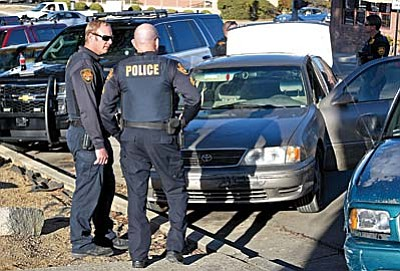 Matt Hinshaw/The Daily Courier<br /><br /><!-- 1upcrlf2 -->Prescott police officers inspect a vehicle that was allegedly involved in a collision with a skateboarder at an alley between Marina and Cortez Wednesday afternoon in downtown Prescott.