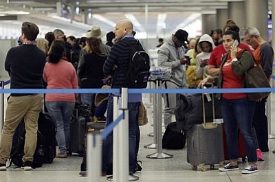 Sonny McManus, of Nashville, Tenn., right, waits in line to reschedule her flight at Miami International Airport, after her flight to Nashville was canceled, Friday, Jan. 22, 2016, in Miami.(AP Photo/Lynne Sladky)