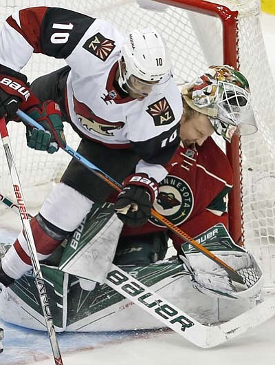 Minnesota Wild goalie Devan Dubnyk, right, loses his helmet as Arizona Coyotes' Anthony Duclair collides with him after he was hooked by Mikael Granlund in the third period Monday, Jan. 25, in St. Paul, Minn. The Coyotes won 2-1 in a shootout. (AP Photo/Jim Mone)