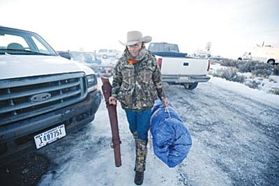 Rick Bowmer/The AP<br> Arizona rancher LaVoy Finicum carries his rifle after standing guard all night at the Malheur National Wildlife Refuge on Jan. 6 near Burns, Oregon.  Finicum was killed during an incident Jan. 26 that also saw the arrest of the standoff's leadership.