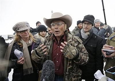 "LaVoy Finicum, a rancher from Arizona, who is part of the group occupying the Malheur National Wildlife Refuge speaks with reporters during a news conference at the the refuge Tuesday, Jan. 5, 2016, near Burns, Ore. Law enforcement had yet to take any action Tuesday against the group numbering close to two dozen who are upset over federal land policy. Finicum said the group would examine the underlying land ownership transactions to begin to ""unwind it,"" stating he was eager to leave Oregon. (AP Photo/Rick Bowmer)"
