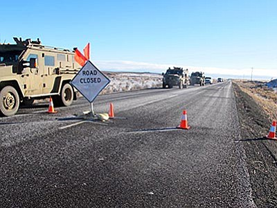 Nicholas K. Geranios/The AP<br> A convoy of armored vehicles and SUVs rolls past a barricade on the road near the Malheur National Wildlife Refuge near Burns, Oregon, Saturday, Jan. 30. The remnants of an armed group occupying the refuge to protest federal land policies say they won't leave until they get assurances they won't be arrested.