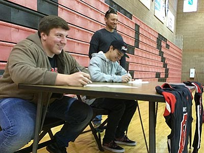 Doug Cook/The Daily Courier<br> Bradshaw Mountain High's Zach Latham, foreground, and Derrik Fabela sign letters of intent to play college football in 2016 on National Signing Day Wednesday, Feb. 3, at Gary Kunow Gym in Prescott Valley. Chris Fabela, Derrik's father, looks on.