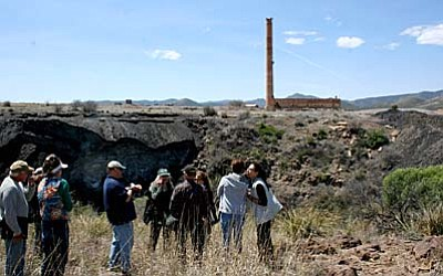 Sue Tone/The Daily Courier, file<br>The Humboldt smelter stack overlooks the contaminated slag pile on the left and the dross pile on the right, both extending to the Agua Fria River. Community members and EPA officials toured this and the Iron King Mine site in April 2015.