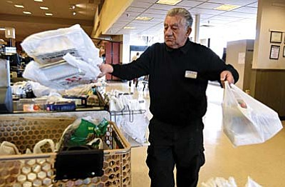 Milenko Rafilovich loads plastic bags full of a customers groceries into their cart at Safeway on Willow Creek Road in Prescott.
