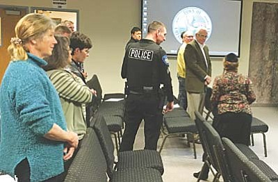 Ken Sain/For The Daily Courier<br>A Chino Valley police officer escorts Rabbi Adele Plotkin, right, out of council chambers after she protested the Christian prayer that Mayor Chris Marley gave at Tuesday's meeting.