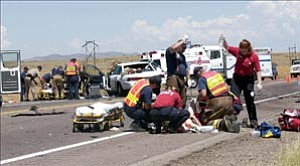 Courier/Jo. L. Keener Prescott Fire Department Paramedics work on one of the multiple patients after a head on collision on Highway 89 north of Prescott Thursday morning. Two persons were airlifted from the scene to area hospitals, one person died in the wreck.