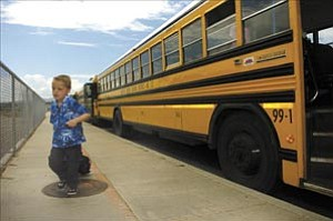 Courier/Les Stukenberg Wyatt Dutton runs to catch his dad Monday after checking out which bus to ride home after his first day of school in kindergarten at Coyote Springs Elementary School in Prescott Valley.