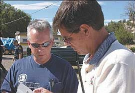Courier/Les Stukenberg Soon-to-be Prescott Fire Deputy Chief Bruce Martinez, right, and Battalion Chief Don Devendorf look at a photocopy of the photo of a missing five-year old Monday afternoon. Martinez will replace retiring Chief Paul Laipple in November.