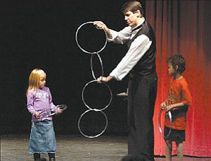Courier/Nathaniel Kastelic Magician and comedian Mark Robinson, center, performs a hoop magic trick with the help of Carissa Evans and Brendon Allen Sunday afternoon at Glassford Hill Middle School in Prescott Valley.