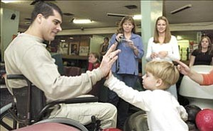 Courier/Nathaniel Kastelic Prescott Police officer Robb Martin high fives Alexander Sam, the son of close friend Marcus, after almost bowling a strike Saturday afternoon at his Bowlathon Benefit at Plaza Bowl in Prescott. In the background wife Lisa, left, films the occasion as daughters Machelle and Rebecca look on.