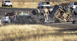 Courier/Nathaniel Kastelic Prescott Valley Police, Department of Public Safety and Yavapai County Sheriff¹s officers investigate the wreckage of a two-vehicle accident on Highway 69 near Fain Road that resulted in three deaths late Sunday afternoon in Prescott Valley. Authorities closed the highway westbound at Fain Road for several hours.