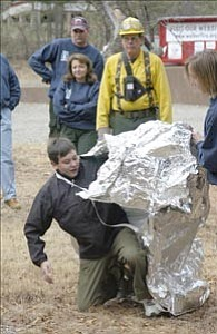 Courier/Jo. L. Keener Wes Overmyer, 13, crawls out from under a protective fire shelter Saturday, as Walker Fire¹s Bill Morgan watches. Scottsdale Troop 316 learned fire safety to qualify for their merit badges.