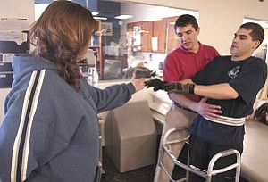 Courier/Les Stukenberg Jeremiah Jorgensen helps Prescott Police Officer Robb Martin maneuver around the therapy room at one of his physical therapy sessions at the Center for Physical Excellence in Prescott. Martin uses the wheel walker and knee-ankle-foot orthoses to put weight on his joints and bones for short periods of time to try to help keep them healthy.