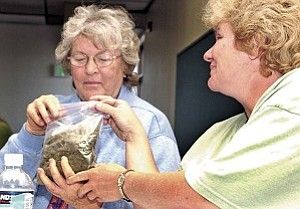 Kim Pratt, right, holds a bag of marijuana for Mary Hill to smell and become more familiar to the sight and smell of the drug at the ŒDrugs 101¹ meeting Thursday afternoon at the Dexter Family Resource Center in Prescott. Courier/Nathaniel Kastelic