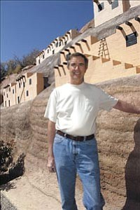 Wayne Cramer poses underneath his replicas of Indian Pueblos Wednesday at his Prescott home. The Pueblo¹s are designed as part of an erosion control project at the rear of his Cliff Rose home. Cramer has created a wall with cement and the decorative Pueblos to stop erosion at the back of his home.  Courier/Jo. L. Keener
