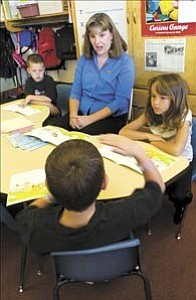 Courier/Les Stukenberg  Miller Valley Elementary School second-grade teacher Kris Foster listens as one of her students tells her about his experience with a crawdad. Pictured along with Foster are students Cody Carey, left, Caterina DeLeon, right, and Noah Henen, with back to camera.